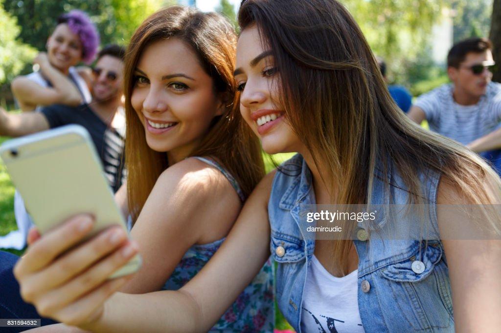 Beautiful girls taking selfie photos outdoor : Stock Photo