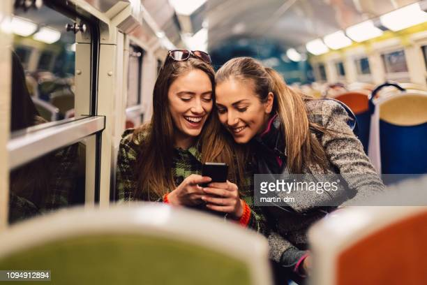 beautiful girls traveling in subway train and having fun in social media - subway train stock pictures, royalty-free photos & images