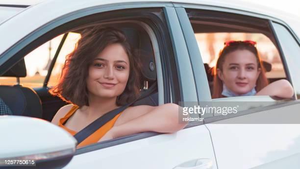 コロナウイルスcovid-19アウトブレイク中に医療マスクを着用した美しい女の子。保護医療マスクを着用したドライバーの肖像。車の中で微笑む若い友人。 - 西暦2000年 ストックフォトと画像