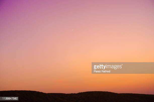 beautiful golden and purple sky and silhouette - avondschemering stockfoto's en -beelden