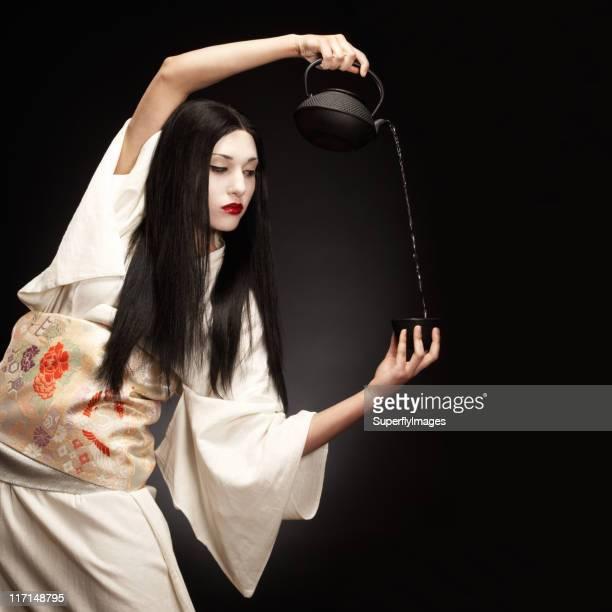 Wunderschöne, elegante Geisha Frau gießen Tee in weißen Kimono