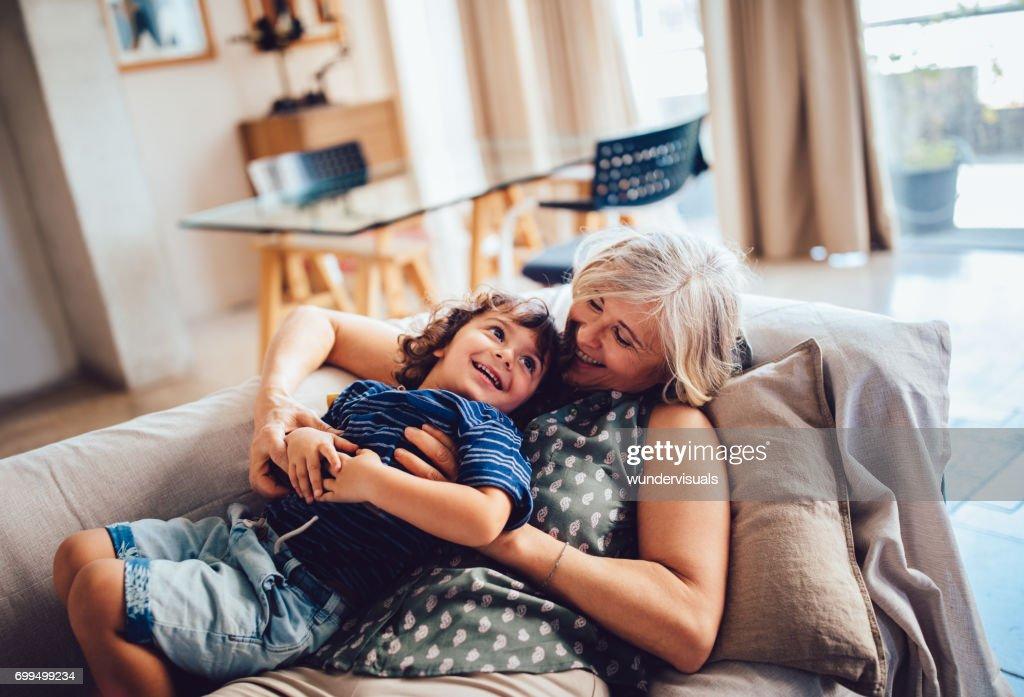 Beautiful grandma and grandson playing together having fun at home : Stock Photo
