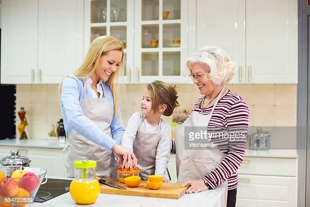 Bela avó, mãe e filha preparar novas Sumo de Laranja