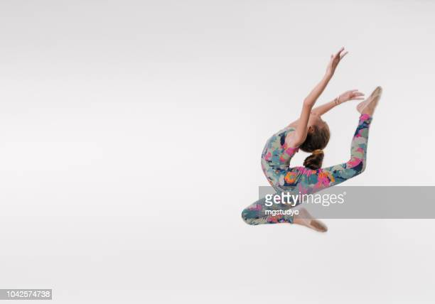beautiful gymnast athlete teenage girl  jumping in studio - acrobatic activity stock pictures, royalty-free photos & images