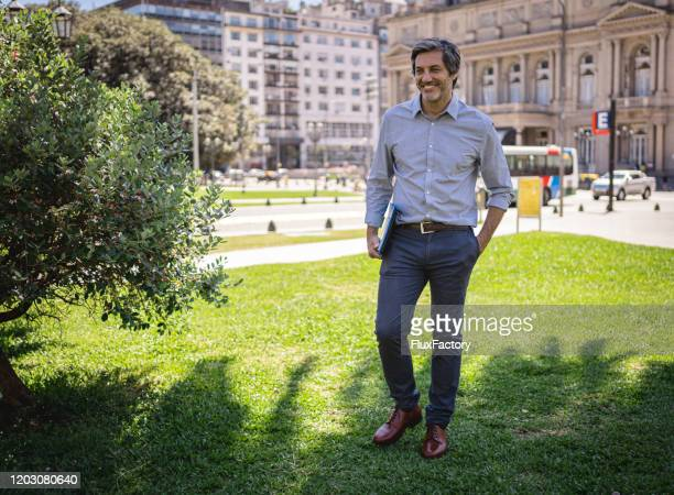 beautiful handsome businessman walking in the park - one man only stock pictures, royalty-free photos & images