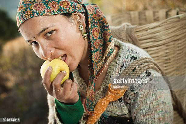 Beautiful, happy, Asian young woman carrying basket and eating apple.