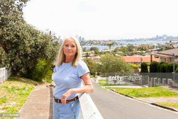 Beautiful happy blond mature woman standing in sunshine