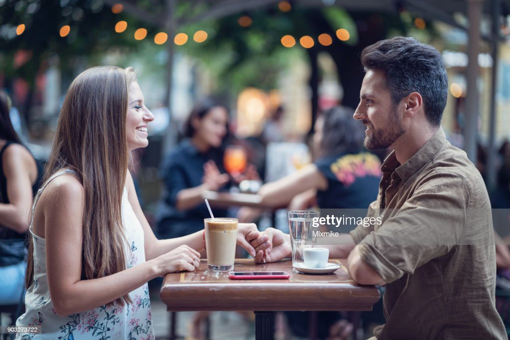 Beautiful happy couple dating outdoors in a café : Stock Photo