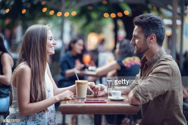 Beautiful happy couple dating outdoors in a café