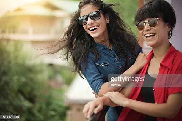 Beautiful happy female friends of different ethnicity in balcony.