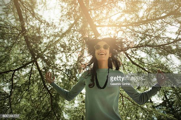 Beautiful, happy girl expressing freedom and jumping under pine trees.