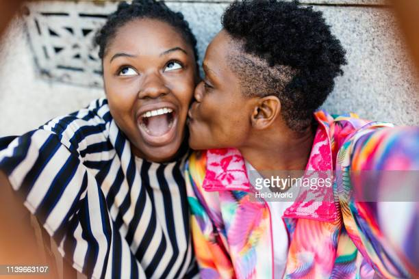 Beautiful happy girlfriends taking a kissing on the cheek selfie with mobile phone