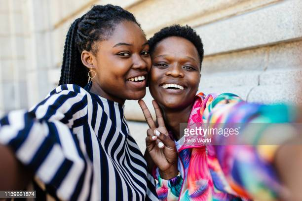 beautiful happy girlfriends taking a selfie whilst showing victory sign with hands - sister stock pictures, royalty-free photos & images