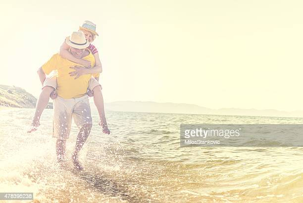 Beautiful Happy Mature Couple have fun on the beach