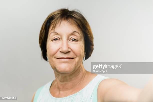 Beautiful happy mature woman taking selfie