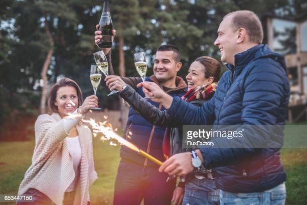 beautiful happy people celebrate with champagne outdoors