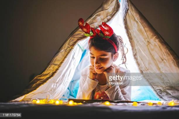 hermosa chica sonriente feliz ytendiendo en la cama / decoraciones de navidad - historia fotografías e imágenes de stock