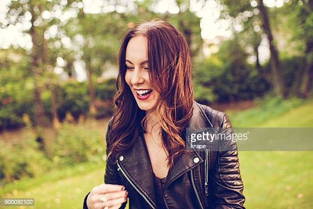Beautiful happy woman in park laughing
