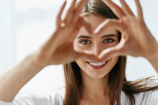 Beautiful Happy Woman Showing Love Sign Near Eyes. 943085232