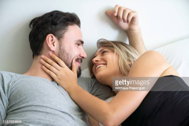 beautiful happy young couple lying on bed and hugging - amanti letto foto e immagini stock