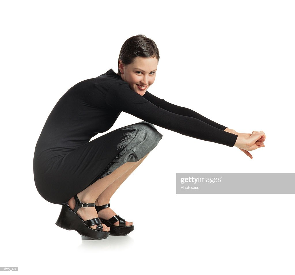 beautiful happy young woman with short dark hair slicked back bends over and crouches with arms stretched out in front of her turns from the side to look at the camera and smile while wearing a sexy black dress and black sandals : Foto de stock