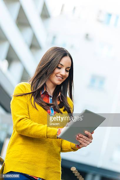 Beautiful hard-working modern businesswoman using digital tablet and smiling