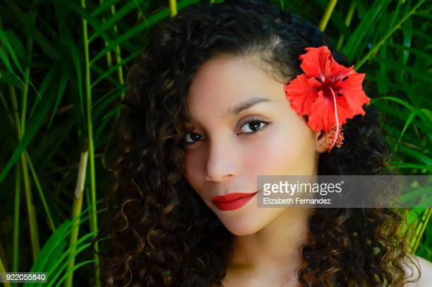 Beautiful headshot of a young woman with a flower in her ear