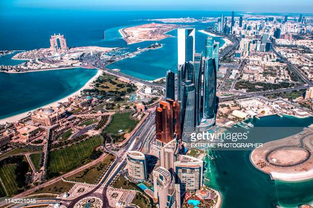 beautiful high angle view of modern skyscrapers in abu dhabi, taken from a helicopter. marina is also visible further back - abu dhabi stock pictures, royalty-free photos & images