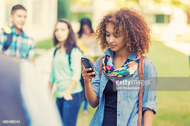 beautiful high school student using smart phone outdoors - beautiful black teen girl stock photos and pictures