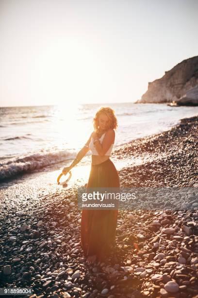 beautiful hippie woman at beach music festival playing the tambourine - tambourine foto e immagini stock