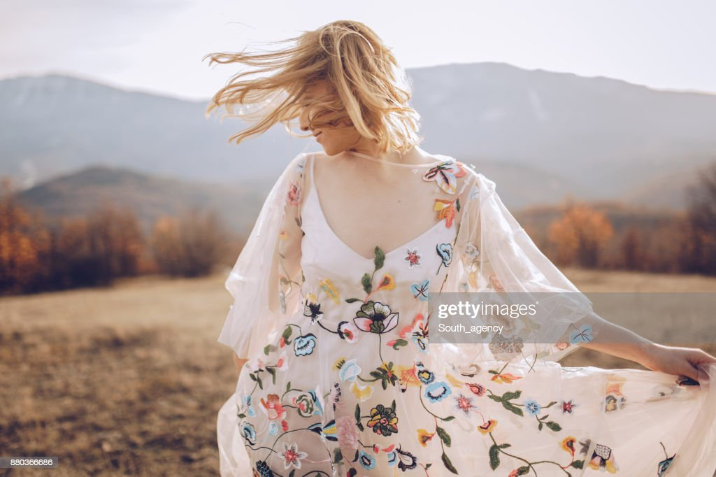 Beautiful hippie woman dancing in a meadow : Stock Photo