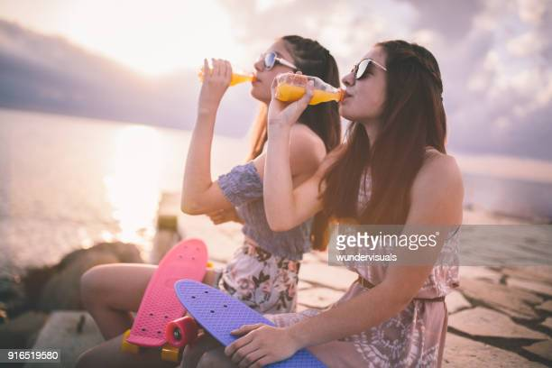 beautiful hipster teenage girls drinking soda at the beach - juice drink stock photos and pictures