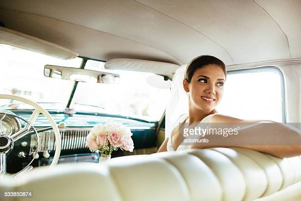 Beautiful Hispanic bride looking back in a classic car