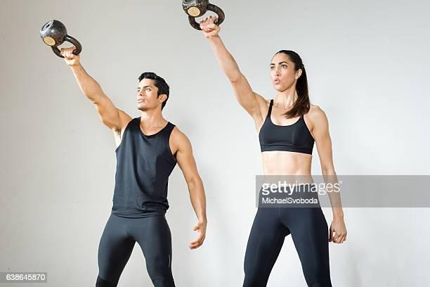 Beautiful Hispanic Couple Lifting Kettlebells Together