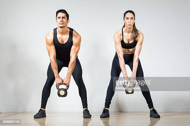 Beautiful Hispanic Couple Lifting Kettlebells Together