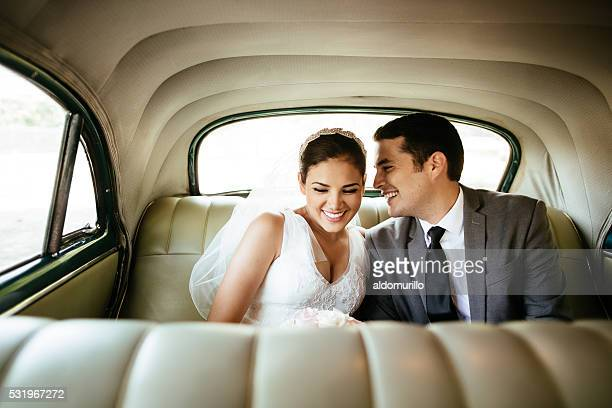 beautiful hispanic newlyweds laughing in backseat - newlywed stock pictures, royalty-free photos & images