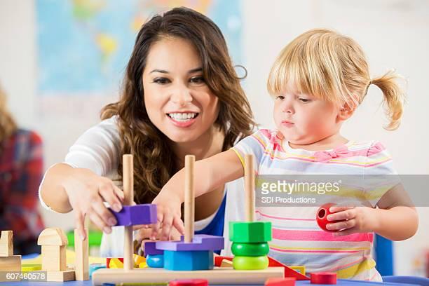 Beautiful Hispanic teacher works with cute blonde preschooler