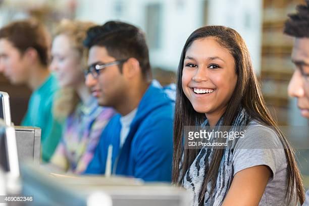 Hispanic teen girl hermoso usando el ordenador en high school laboratorio