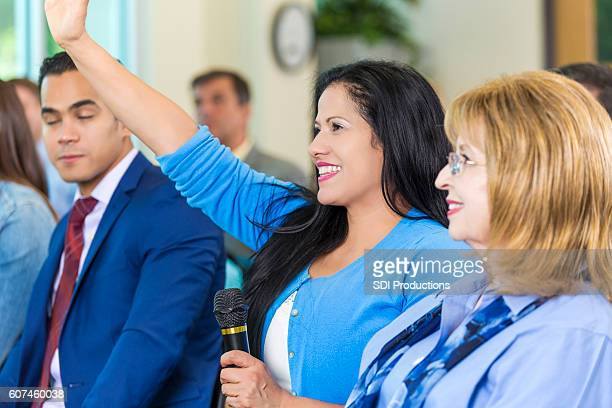 beautiful hispanic woman raises her hand during meeting - town hall meeting stock photos and pictures