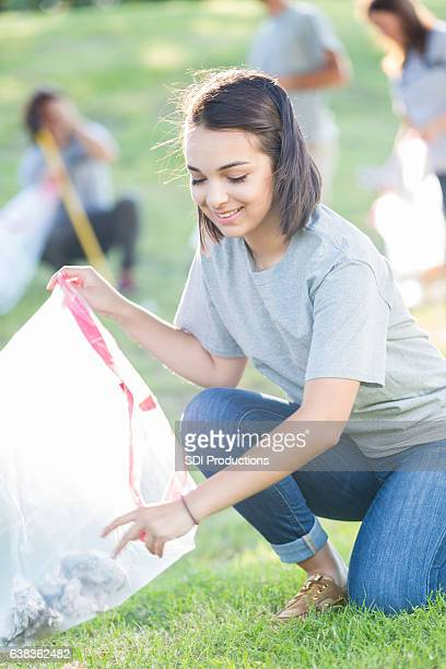 Beautiful Hispanic young woman participates in neighborhood cleanup