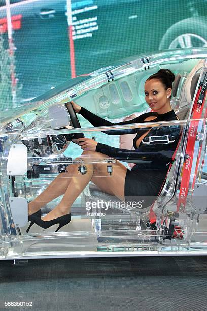 Beautiful hostess in a transparent car