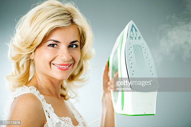 Beautiful housewife holding iron and looking at camera
