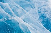 Beautiful icy snowy blue texture. The surface of a winter lake, reservoir. Frozen snow water.