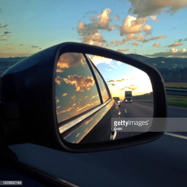 beautiful image of road at sunset by car rear view mirror. photo taken with iphone. - rear view mirror stock pictures, royalty-free photos & images