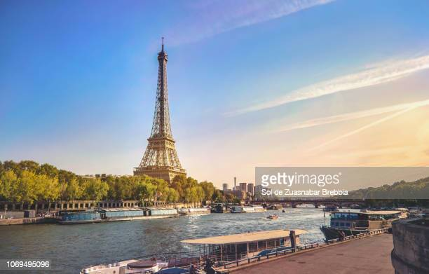 beautiful image of the eiffel tower and the seine in a magnificent sunny day - eiffel tower paris stock pictures, royalty-free photos & images