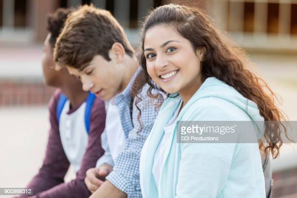 Beautiful Indian American teen girl smiling at camera while outside high school with friends