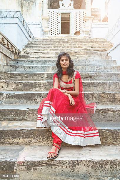 Beautiful indian bollywood model sitting on stairway of Jagdish Temple