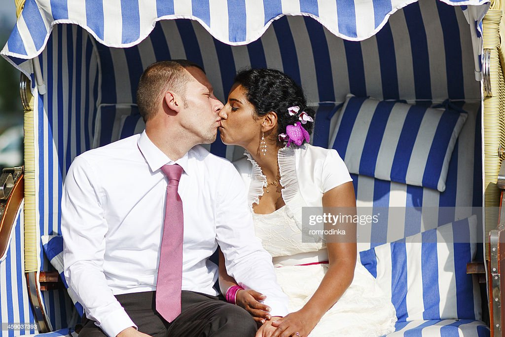 Beautiful Indian Bride And Caucasian Groom In Beach Chair Stock