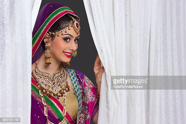 Beautiful Indian bride smiling amidst curtains