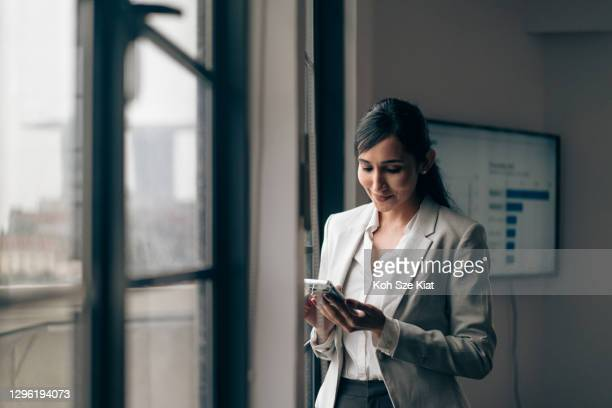 beautiful indian businesswoman using her mobile phone in the office - businesswear stock pictures, royalty-free photos & images